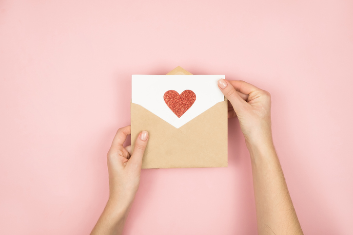 Love letter in women hands on Valentines Day. Handmade postcard with red heart on pink background. 14 February concept